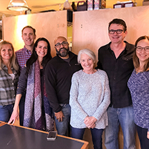 Members of JSK Partners volunteer at the Potluck Café in Vancouver, British Columbia. From left to right: Jessica Dewey, Tyler Steele, Heather Meehan, Neil Kumar, Wendy Lloyd, Dwight Jefferson, Brenda Geib.